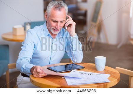 Involved in work. Pleasant content senior man holding papers and talking on cell phone while working in the cafe