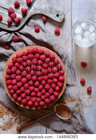 Homemade delicious tiramisu cake with fresh raspberries and cold lemonade on the rustic wooden table. Concept of a romantic breakfast. Horizontal top view.