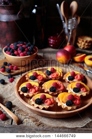 Fresh berry tartlet or cake with vanilla custard, raspberry, peach and blackberry delicious dessert for the whole family and easy diet. Rustic style. Close up.
