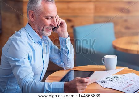 Work with pleasure. Positive smiling senior man sitting at the table and talking on cell phone while holding papers