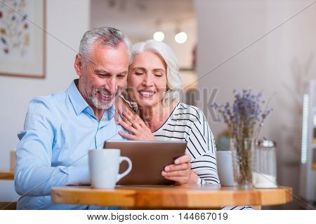Nice time together. Cheerful content senior couple smiling and using tablet while sitting in the cafe