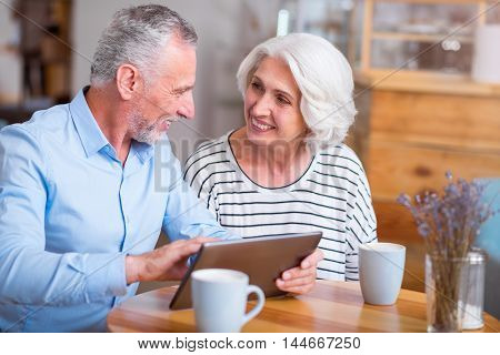 Life with positivity. Cheerful content senior couple smiling and using tablet while resting together in the cafe