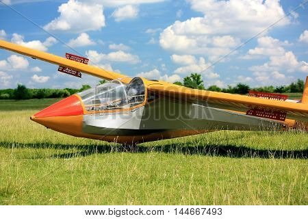 Hungarian glider airplane on grass runway with cloud sky