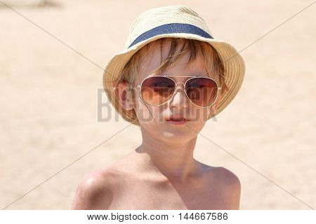 Boy 9 years old in a hat and sunglasses posing on the beach