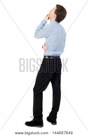 back view of standing business man. curly-haired businessman in light shirt looking up thoughtfully.
