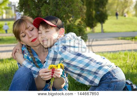 Mother and son in the park on the grass the son gives flowers