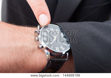 Male Manager Pointing Watch In Closeup