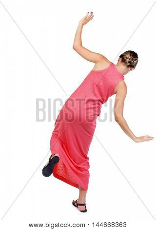 Balancing young woman. or dodge falling woman. slender woman in a long red dress is trying to stand on the leg.