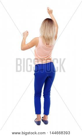 back view of dancing young beautiful woman. girl watching. Isolated over white background. Blonde in blue pants waving dancing raising his hands.