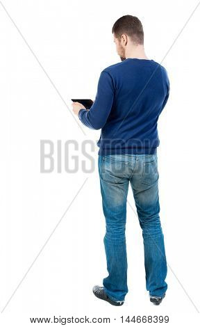 back view of business man uses mobile phone. bearded man in blue pullover reads from the tablet.