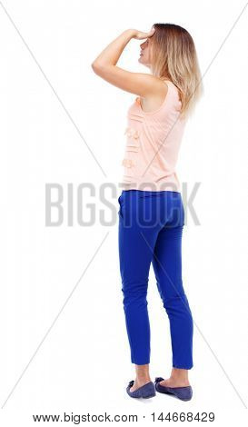 back view of standing young beautiful woman. Blonde in blue pants looks into the distance put her hand to her eyes.