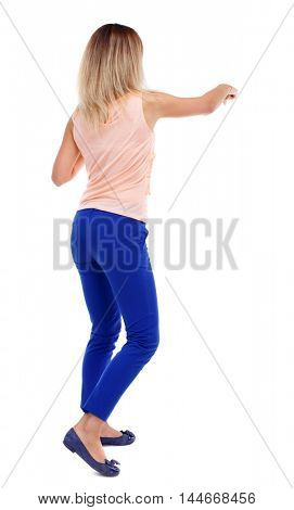 back view of standing girl pulling a rope from the top or cling to something. Rear view people collection. backside view of person. Isolated over white background. The blonde in a pink t-shirt hand