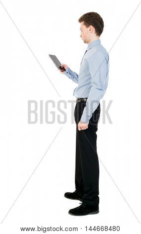 back view of business man uses mobile phone. rear view people collection. curly-haired businessman in light shirt stands sideways and read e-books.