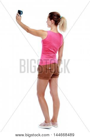 back view of standing young beautiful woman and using a mobile phone. Isolated over white background. Sport blond in brown shorts makes mobile camera selfie.