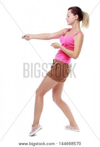 back view of standing girl pulling a rope from the top or cling to something. Isolated over white background. Sport blond in brown shorts pulls the rope something.