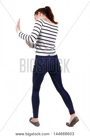 back view of woman pushes wall. Isolated over white background. Girl in a striped sweater pushing something in front of him.