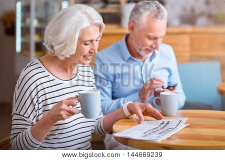 Every day life. Cheerful pleasant senior woman reading newspaper and her husband using cell phone while drinking coffee in the cafe together