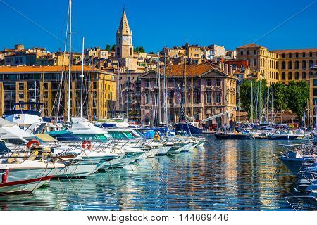 The blue water reflects the ancient buildings on the waterfront. Rows of sailing yachts, motor boats and fishing boats. The Marseille Old Port