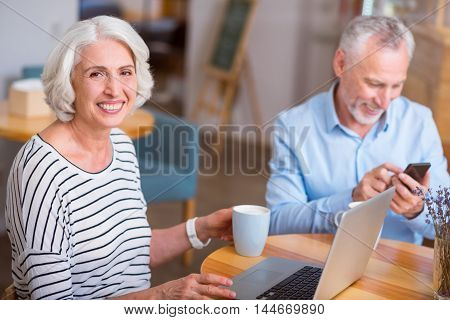 Positive emotions. Cheerful content senior woman using laptop and resting in the cafe with her husband who is using cell phone