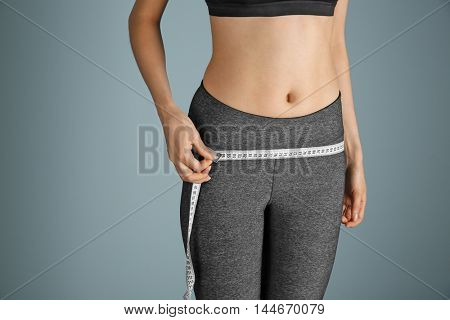 Girl with measure tape on grey background