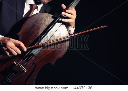 Man playing cello in darkness