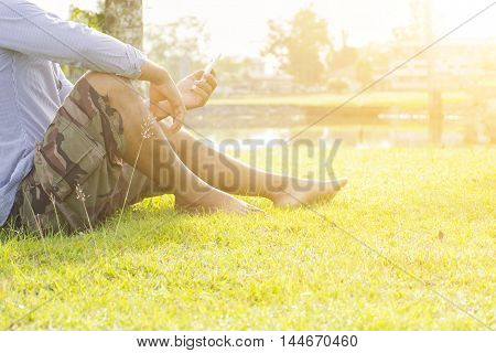 Male holding smartphone in his hand.And background of nature outdoor and sunshine view.
