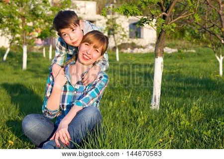 Mother and son sitting on the grass in the park