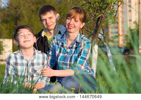 Family of three people sitting on the grass in the park