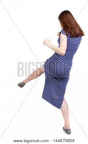 skinny woman funny fights waving his arms and legs. Isolated over white background. The brunette in a blue striped dress stands sideways beats foot.