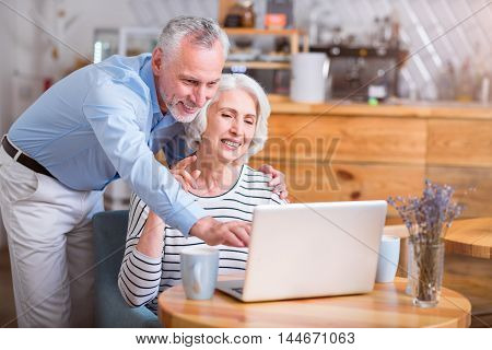 Teach me how it works. Cheerful delighted senior couple using laptop and smiling while resting in the cafe