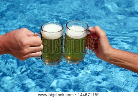 happy friends drinking beer and clinking glasses