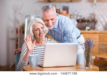 Modern way of communication. Cheerful senior couple using laptop and talking through the Internet while resting in the cafe