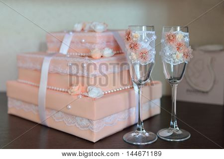 Two fancy wedding glasses with decorated box on background. Carrot color