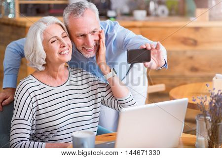 Have some fun. Cheerful delighted senior couple smiling and making selfie while resting in the cafe