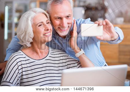 Nice time. Cheerful delighted loving senior couple making selfies and smiling while resting in the cafe