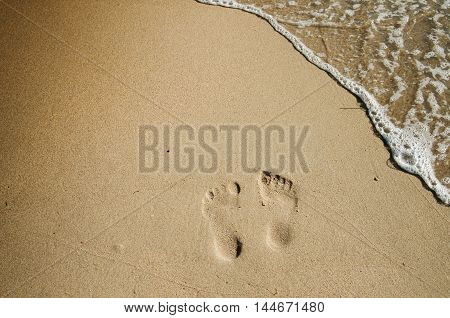 Two footprints on the beach in the sand