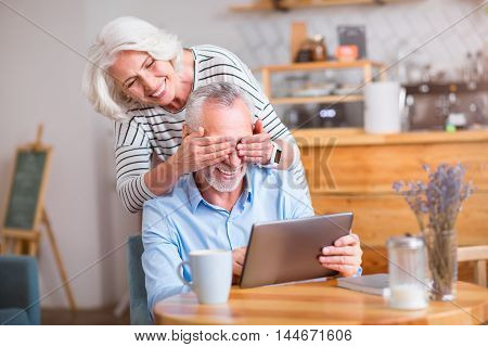 Guess who. Positive smiling senior woman closing eyes of her husband who is sitting at the table and using tablet