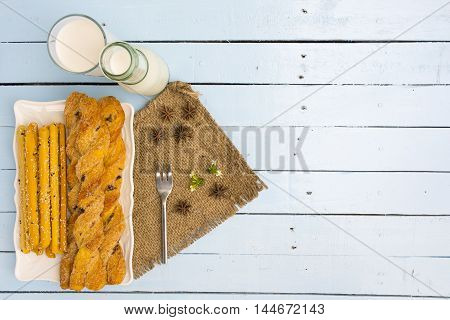 Breadsticks and milk on sky blue table background.Snack with meal or food of relax and holiday.Top view.