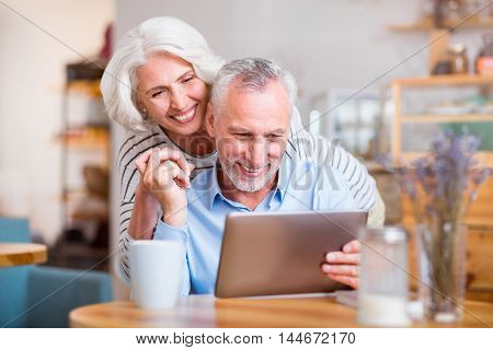 Happiness in everyday things. Cheerful loving positive couple using tablet and embracing while resting together