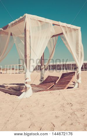 Gazebo on the beach with white curtains in the sand against the blue sky (vintage)