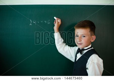 Student writing on the blackboard with chalk