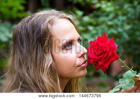 Portrait of a beautiful girl with a red rose