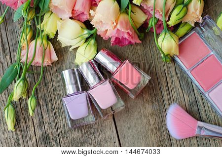 Nail polish, blush and brush on a wooden table on a background of beautiful flowers. Women's cosmetics