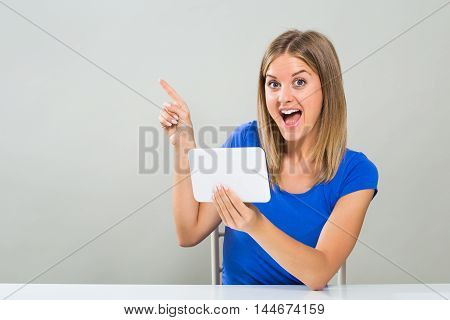 Excited young woman is pointing while using digital tablet.