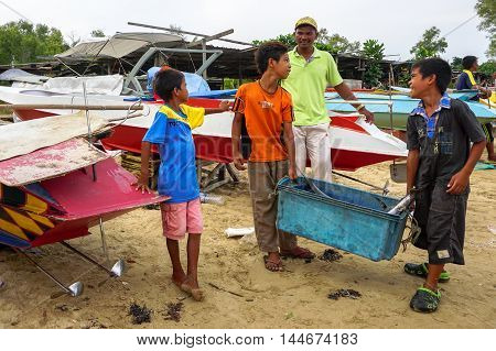 Labuan,Malaysia-Aug 28,2016:Unidentified kids of fishermen carry the catch to the shore at Kiansam village on 28th Aug 2016 in Labuan.This village is among famous place to see fisherman life in Labuan