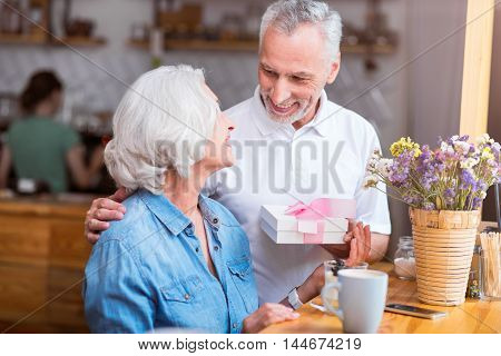For you my love. Pleasant smiling woman sitting at the table while her husband giving her a present while resting in the cafe together
