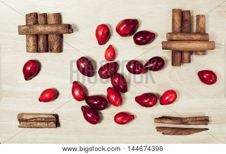Red dogwood berries and cinnamon still life food on wooden background in minimalism style