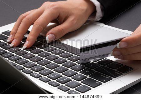 Young office woman in the black suite and with manicure is typing with one hand on the laptop keyboard and holding bank credit card with another one.