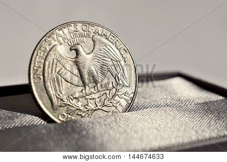 Macro detail of a silver coin of One American Dollar (USD, United States of America Dollar) placed in the gray luxurious jewelry gift box as a symbol of luxury and highly appreciated American currency