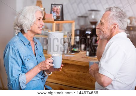 Rest a bit. Cheerful delighted senior couple drinking coffee and talking while standing in the cafe